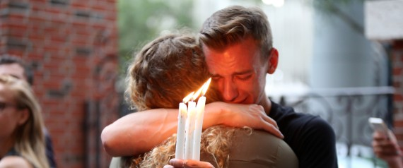 Brett Morian, from Daytona Beach, hugs an attendee during the candlelight vigil at Ember in Orlando, Fla., on Sunday, June 12, 2016. (Joshua Lim/Orlando Sentinel via AP)